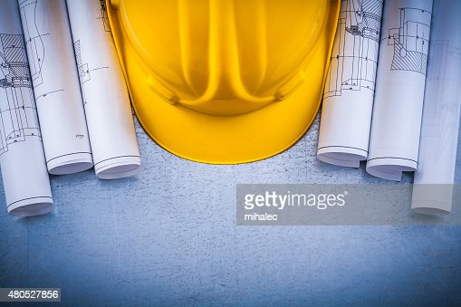 Scratched metallic surface with blueprint rolls and building hel : Stock Photo
