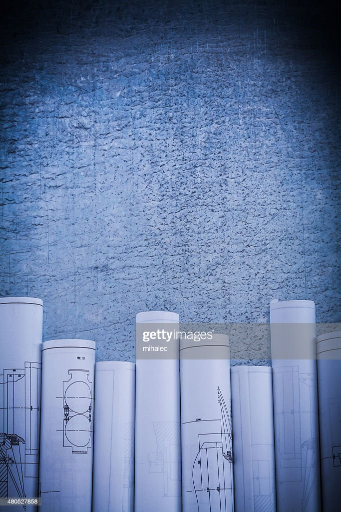 Scratched metallic surface with blueprint rolls construction con : Stock Photo