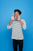 Portrait of excited afro american guy wearing striped long sleeved t-shirt and black trausers, scraming. Studio shot, blue background.
