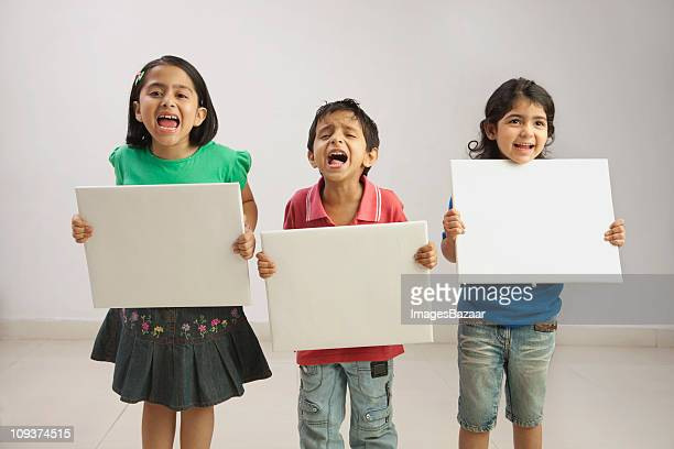 Screaming girls (4-5, 6-7) and boy (4-5) holding white boards