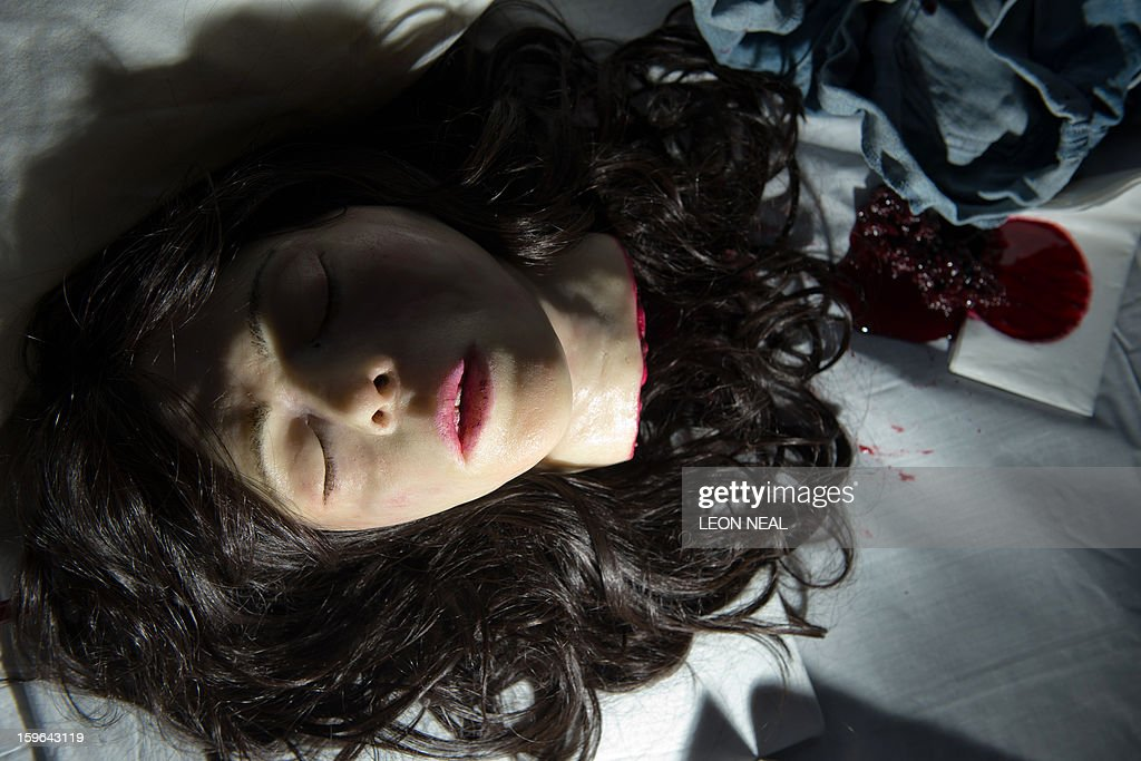 A 'Screaming head' orange drizzle cake with marzipan skin and berry fruit blood is displayed at a film set pop-up experience in east London on January 17, 2013. The event was held to promote the release of a new horror film 'The Helpers'. AFP PHOTO / LEON NEAL