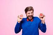 Screaming man holding sour fruit