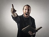 Screaming priest in black clothes, with a book in his hand
