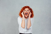 Screaming stressed. Portrait frustrated shocked redhead business woman yelling eyes closed hands on head temper tantrum isolated grey wall background. Negative human emotion facial expression reaction