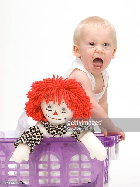 Screaming toddler in basket looking at camera w/mouth wide open