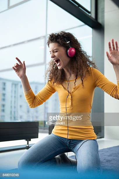 Screaming young woman wearing headphones at the window