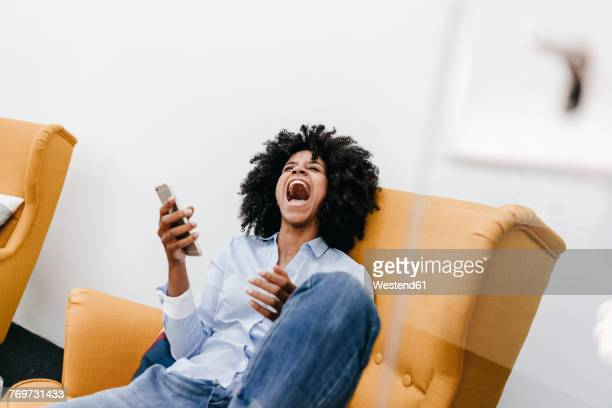 Screaming young woman with cell phone sitting in armchair