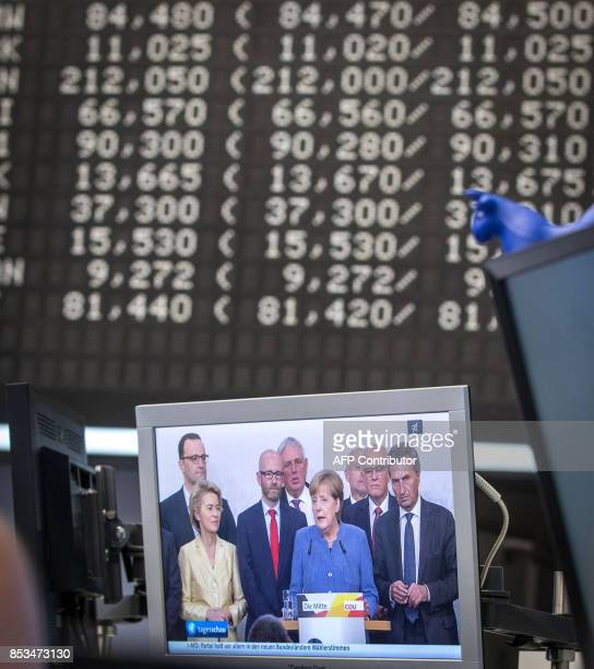 A screen displaying a report on German Chancellor Angela Merkel and general elections in Germany is pictured at the stock exchange in Frankfurt am...