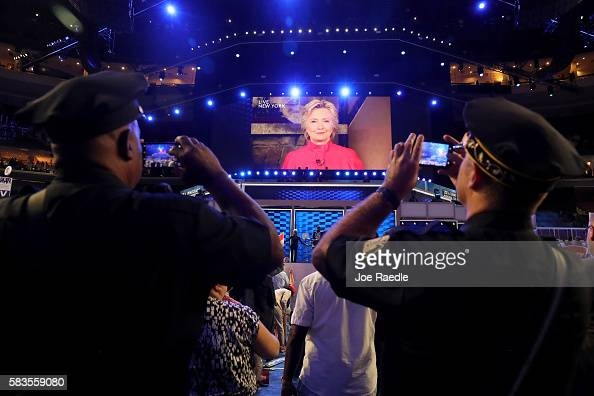 A screen displays Democratic presidential candidate Hillary Clinton delivering remarks to the crowd during the evening session on the second day of...