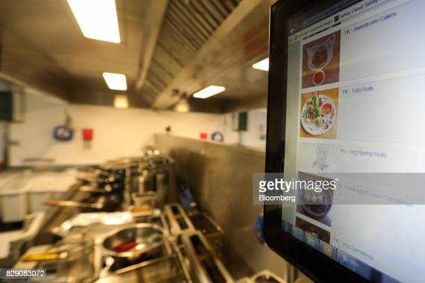 A screen displays menu items for Thaikhun's Thai street food deliveryonly kitchen at a Deliveroo Editions field kitchen operated by Roofoods Ltd in...