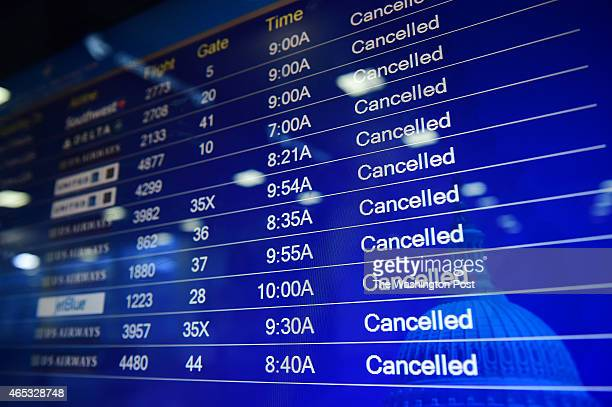 A screen of departing flights shows mass cancellations at Ronald Reagan Washington National Airport on Thursday March 05 2015 in Arlington VA A...