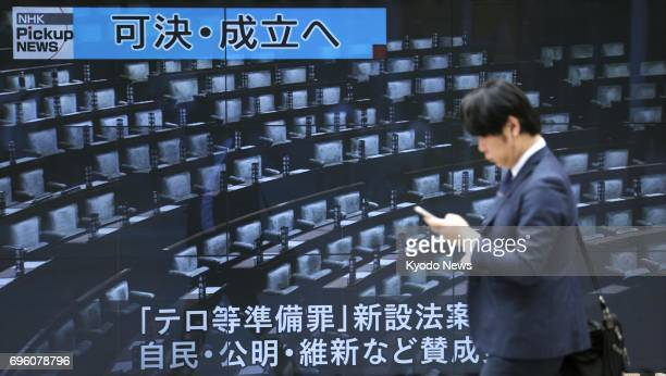 A screen on a Tokyo street shows a news report on June 15 about the parliament enacting contentious legislation to criminalize the planning of...