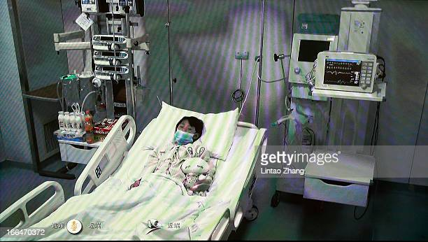 A screen showing a sevenyearold girl who has been infected with the H7N9 strain of bird flu receives medical treatment at Beijing Ditan Hospital on...