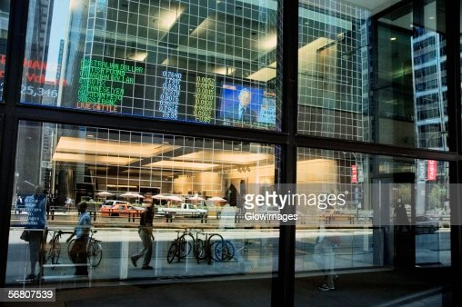 Screen showing currency and market rates through a window of a building