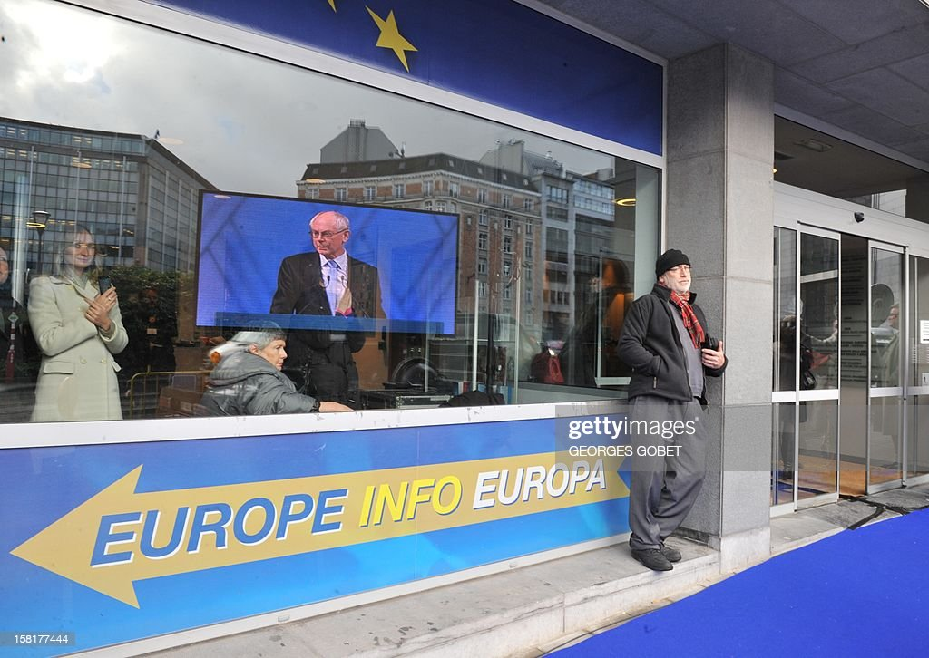 A screen showing EU Council president Herman Van Rompuy during the broadcast of a ceremony for the Nobel peace Prize to European union is reflected on a window in front of the European Council on December 10, 2012 at the EU Headquarters in Brussels. AFP PHOTO GEORGES GOBET