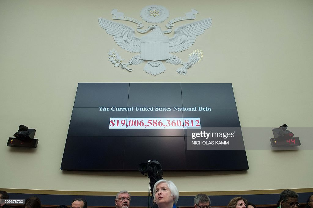 A screen shows the US national debt as US Federal Reserve chair Janet Yellen (front) testifies before the House Financial Services Committee on Capitol Hill in Washington, DC, on February 10, 2016. Federal Reserve Chair Janet Yellen warned that the US economy faces risks from tightening domestic financial conditions as well as global economic turmoil. / AFP / NICHOLAS KAMM
