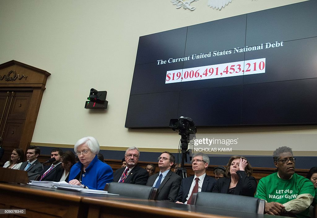 A screen shows the US national debt before US Federal Reserve chair Janet Yellen (front L) testifies before the House Financial Services Committee on Capitol Hill in Washington, DC, on February 10, 2016. Federal Reserve Chair Janet Yellen warned Wednesday that the US economy faced risks from tightening domestic financial conditions as well as global economic turmoil. / AFP / NICHOLAS KAMM