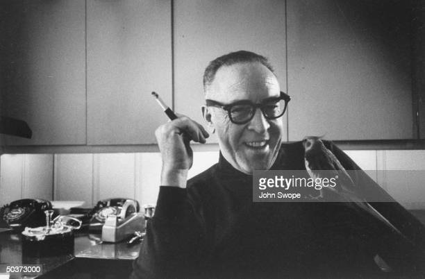 Screen writer and director Dalton Trumbo holding cigarette with his pet bird perched on his chest