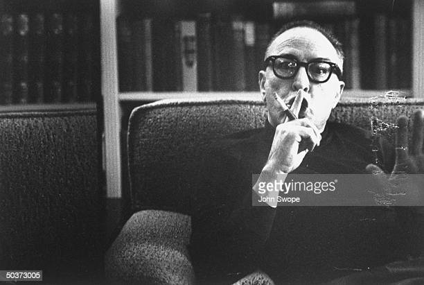 Screen writer and director Dalton Trumbo holding finger up to lips as if to say quiet and waving other hand while sitting on sofa