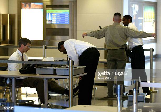A screener for the Transportation Security Administration checks a passenger at a security check point November 18 2002 at Reagan National Airport in...