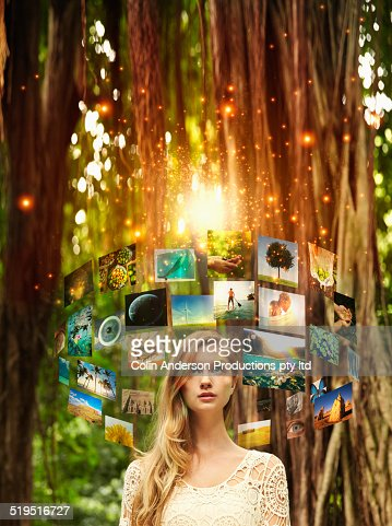 Screens floating around Caucasian woman in forest : Stock Photo