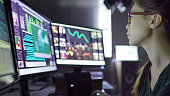 Close up stock image of a young asian woman sitting down at her desk where she's surrounded by 3 large computer monitors displaying out of focus images of people as thumbnails; crowds; graphs & scroll