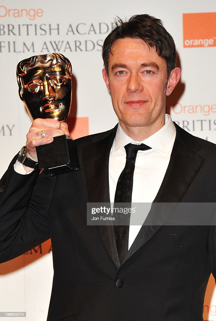 Screenwriter Peter Straughan poses in the press room with the Adapted Screenplay award during the Orange British Academy Film Awards 2012 at the...