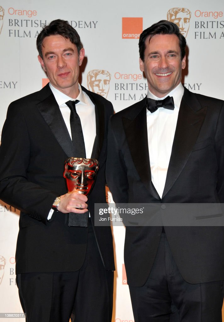 Screenwriter Peter Straughan poses in the press room with the Adapted Screenplay award with actor Jon Hamm during the Orange British Academy Film...