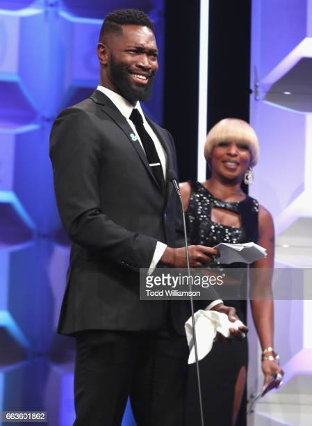Screenwriter Tarell Alvin McCraney accepts award for 'Moonlight' from singer Mary J Blige onstage during the 28th Annual GLAAD Media Awards in LA at...