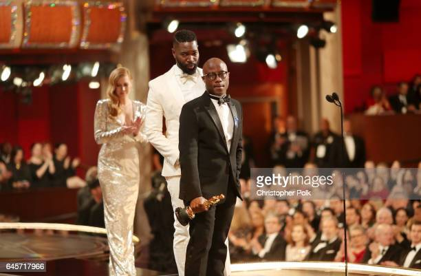 Screenwriter Tarell Alvin McCraney and writer/director Barry Jenkins accept the Best Adapted Screenplay award for 'Moonlight' from actor Amy Adams...