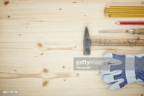 Screwdriver, work glove, pencil, folding ruler, hammer on wood, close up