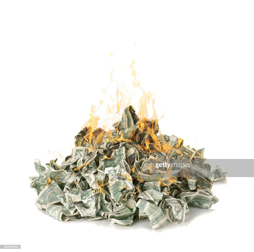 Screwed up dollar notes in a pile on fire : Stock Photo