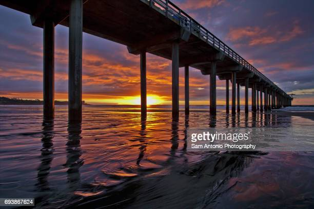 Scripps Pier at low tide with a colorful sunset
