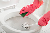 Close up of female hands wearing protective gloves, scrubbing toilet with sponge and brush