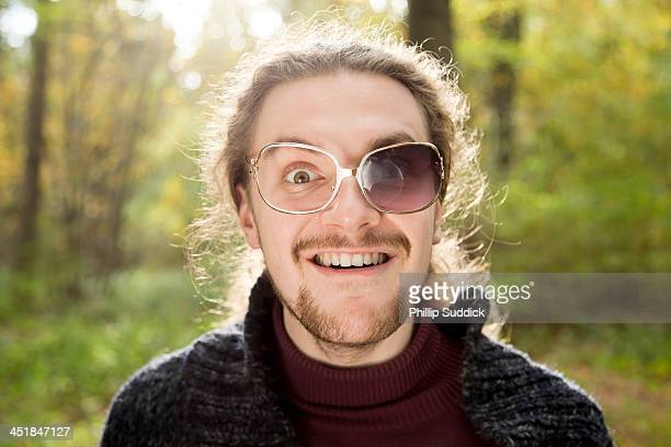 Scruffy boy with broken glasses pulling funny face