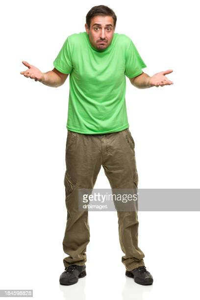 Scruffy man in green t-shirt, shrugging, with palms up