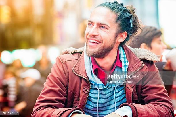 Hört junger Mann blickt auf, lächelt An unseen Freund