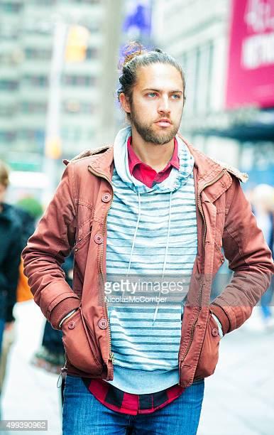Hört junger Mann zu Fuß auf dem Broadway warme Kleidung Mann Brötchen