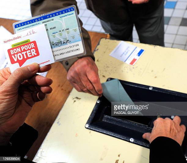 A scrutineer checks the identity card of an elector voting for the second round of French Socialist party primary vote for France's 2012 presidential...