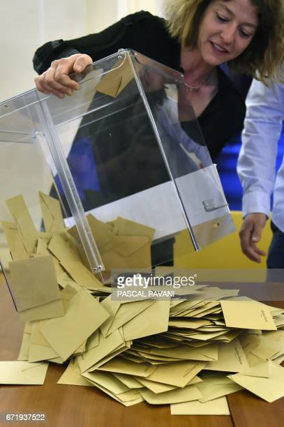 A scrutineer empty a ballot box to count votes at the end of the first round of the French presidential election first round on April 23 2017 at a...