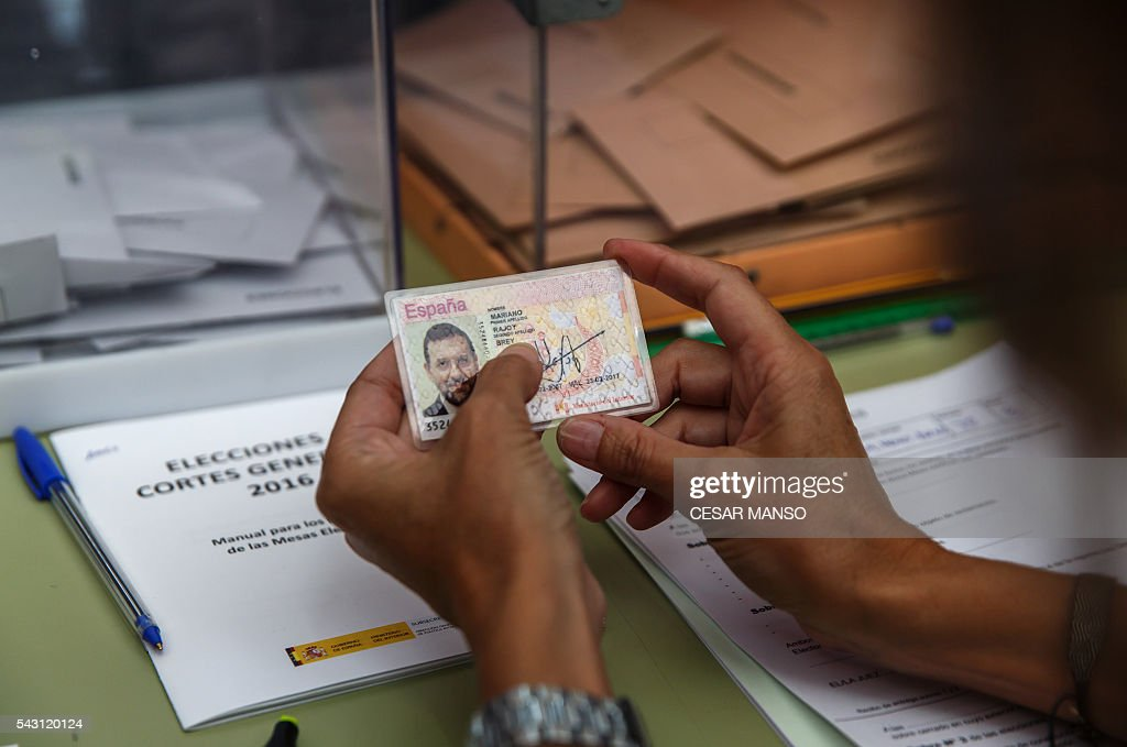 A scrutineer looks at the personal identification (DNI) of Leader of the Popular Party (PP) and Spain's caretaker Prime Minister and party candidate, Mariano Rajoy, before Rajoy's vote in Spains general election at the Bernadette college polling station in Moncloa-Aravaca, Madrid, on June 26, 2016. Spain votes today, six months after an inconclusive election which saw parties unable to agree on a coalition government. MANSO