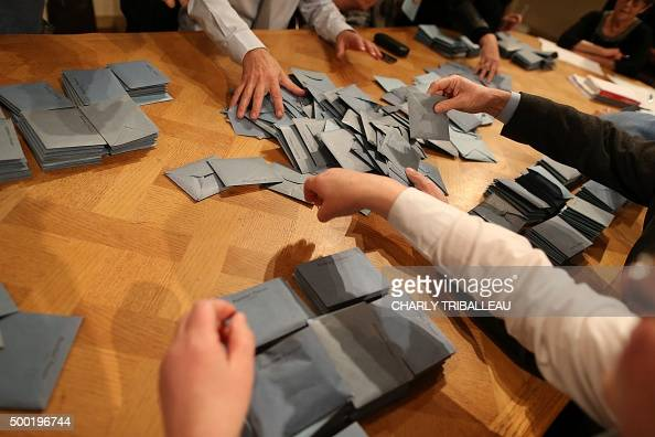 Scrutineers are at work during the votes' counting on the first round of the regional elections on December 6 2015 at a polling station in Épaignes...