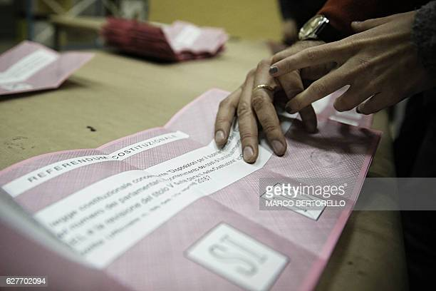 Scrutineers count the ballots at the end of the vote for a referendum on constitutional reforms on December 4 2016 in a polling station in Saluzzo...