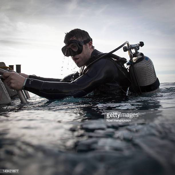 A scuba diver emerges from the water