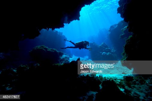 A scuba diver exploring an underwater cave in a tropical coral reef.