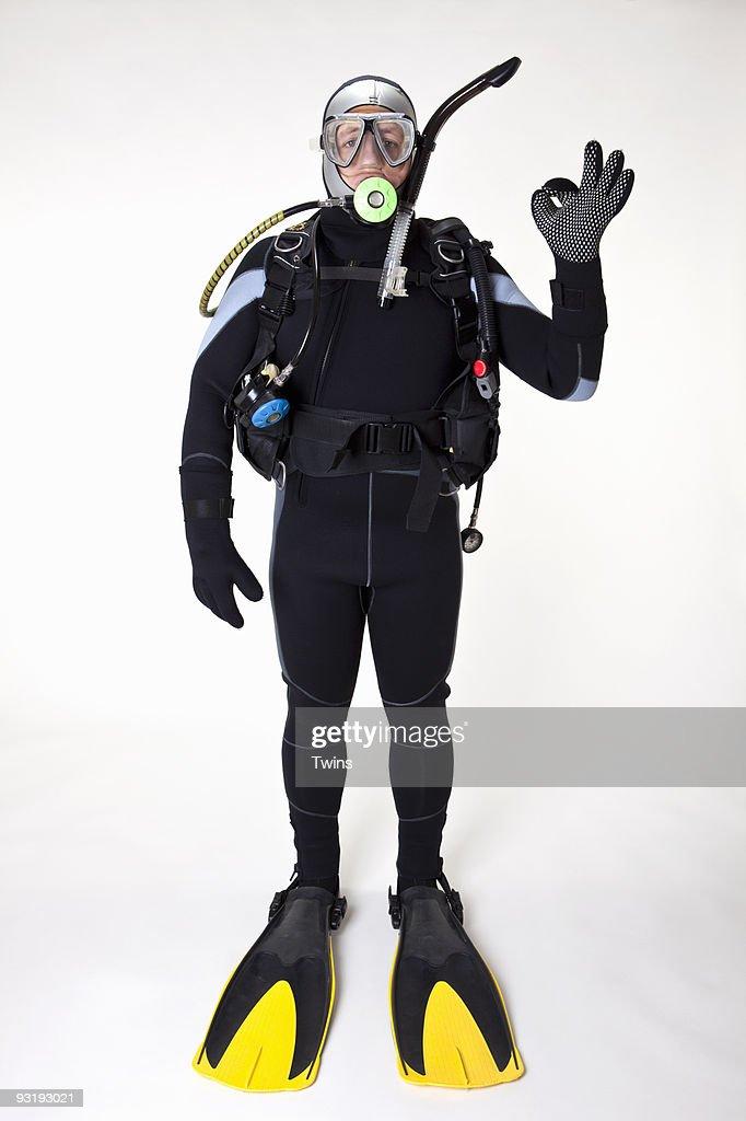 A scuba diver giving the OK sign, studio shot