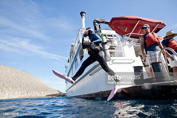 A scuba diver jumps from a dive boat