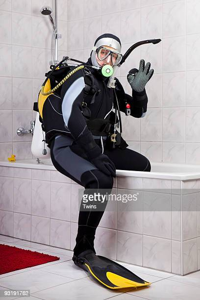 A scuba diver making the OK sign while sitting on the edge of a bathtub