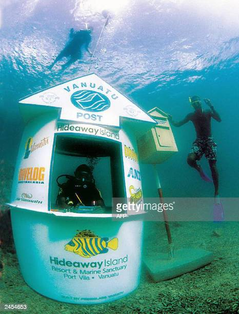 POSTA scuba diver mans the world's first underwater post office as a snorkeller uses the aquatic post box off the coast of Hideaway Island in Vanuatu...