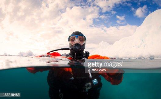 Scuba diver next to an iceberg - split shot